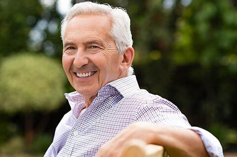 Older smiling man on park bench